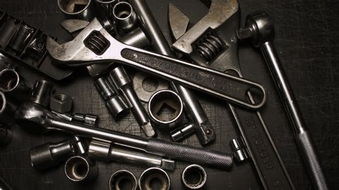 AUTOMOTIVE TOOLS CREATE A THING OF BEAUTY AS A GREASY MALE HAND PICKS UP A WRENCH.  VERSION 2 OF 3.  CLOSE UP.