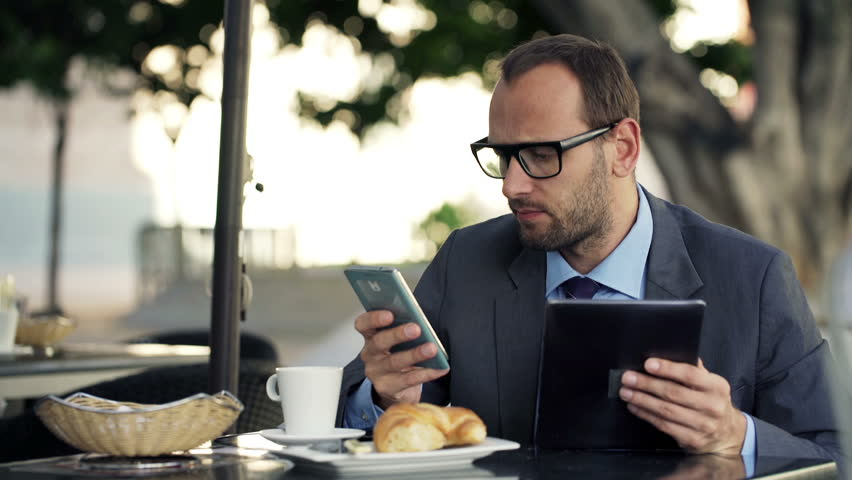 Young businessman comparing data on tablet computer and smartphone in cafe