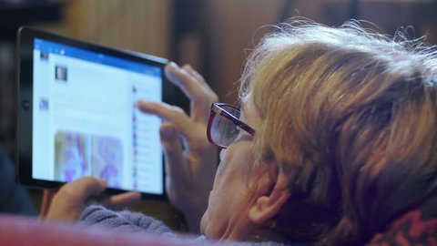 old woman using social networks on tablet computer: facebook, chat, post