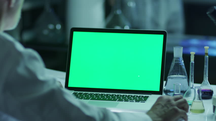 Scientist is using Laptop with Green Screen in Laboratory. Great for Mock-up Usage. Shot on RED Cinema Camera in 4K (UHD). | Shutterstock HD Video #9344909