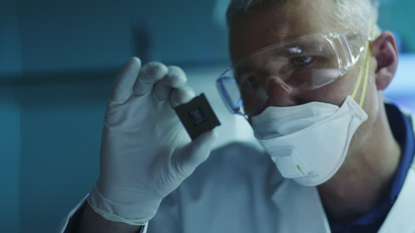 Computer Engineer is Holding and Inspecting Processor Chip. Shot on RED Cinema Camera in 4K (UHD).