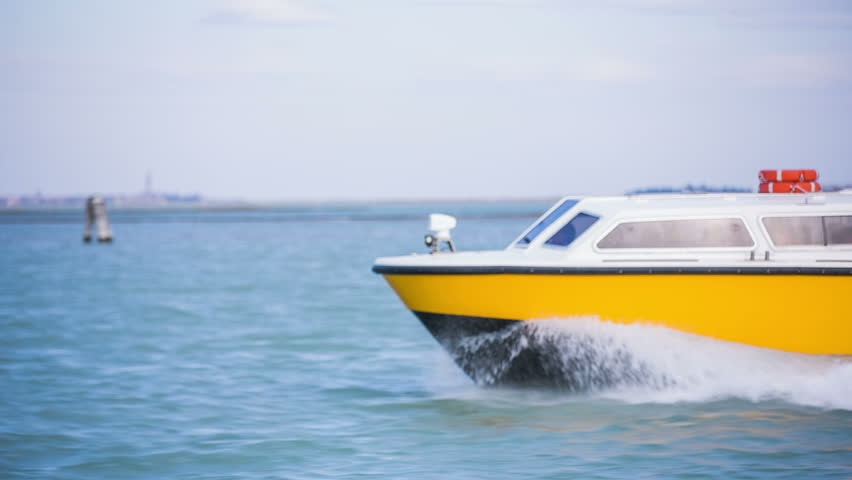 Fast yacht nose cutting through sea. Yellow vessel traveling on sea with people on a sunny day. Riding beside with close up shot.
