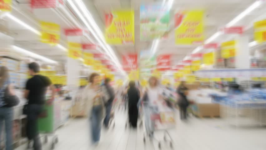 People with shopping carts in a supermarket. Motion blur. Time lapse.