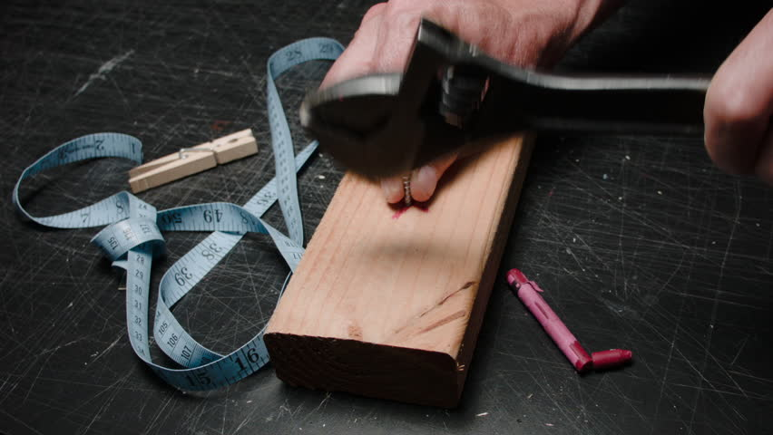 THE WRONG TOOL FOR THE JOB #5.  THE HANDS OF AN IDIOT TRIES TO HAMMER A SCREW, INTO A PIECE OF LUMBER, WITH A WRENCH.   OF COURSE IT FAILS, BUT IT IS ENTERTAINING NEVER THE LESS.  D.I.Y. HUMOR.