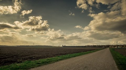 Rural scene taken in between the villages of Sint Odilienberg and Montfort, Limburg, The Netherlands. The power plant of Maasbracht in the background. Time lapse footage with moving clouds.