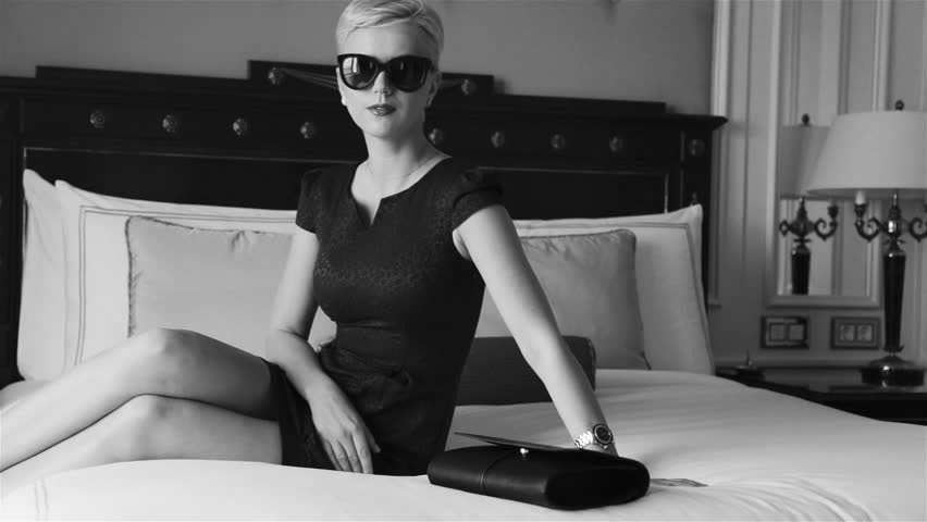 Beautiful sexy blonde business woman wearing skinny short dress jewelry sunglasses in luxury hotel bed room relax rest fashion trend before meeting drink wine do make up red lipstick pillow linens