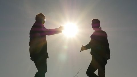 two friends silhouettes meeting with hand shaking and embrace slow motion