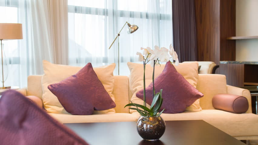 : Luxury apartment interior. View of beautifully decorated living room with beige sofa and orchid on the table with lots of natural light | Shutterstock HD Video #9399791