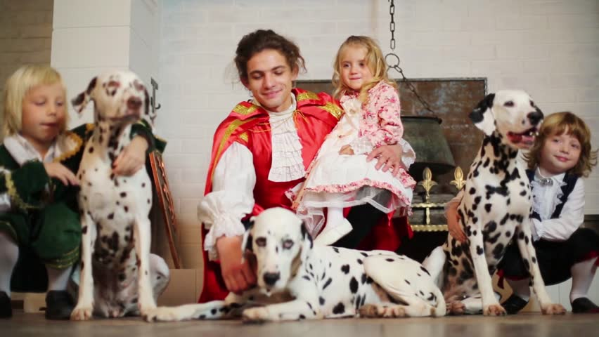 Father in medieval costume with three children and three dalmatians near chimney
