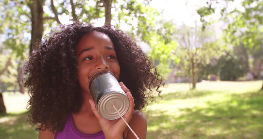 Happy Afro girl talking into a home-made tin can phone outdoors in Slow Motion