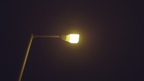 City street lamp flickers turns on after power outage.A street lamp pole turns on and eventually warms up after a power surge.