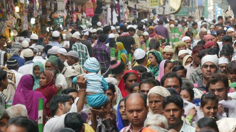 AJMER, INDIA - 30 OCTOBER 2014: Large crowds walk through a busy street towards the Dargah shrine, in Ajmer. Dargah is an important place to visit for Sunni Muslims in India.