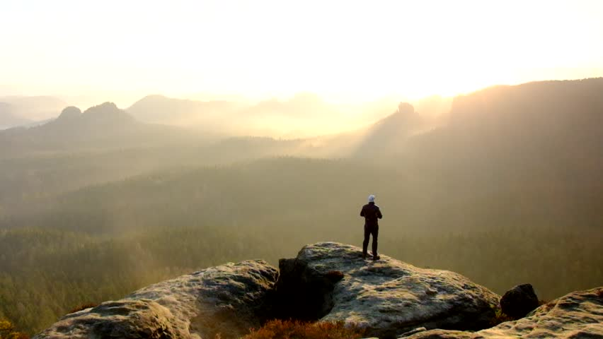 Man takes photos with smart phone on peak of rock empire. Dreamy fogy landscape, spring orange pink misty sunrise in a beautiful valley of Saxony Switzerland park. | Shutterstock HD Video #9497561