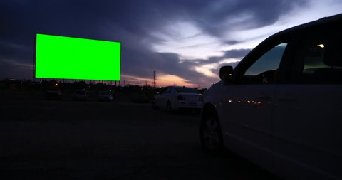 Drive-in movie theater at dusk with green screen -- fill it with anything you want!