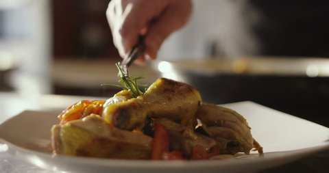 Super slow motion macro of roasted chicken legs with rosemary and grilled vegetables served on a white plate