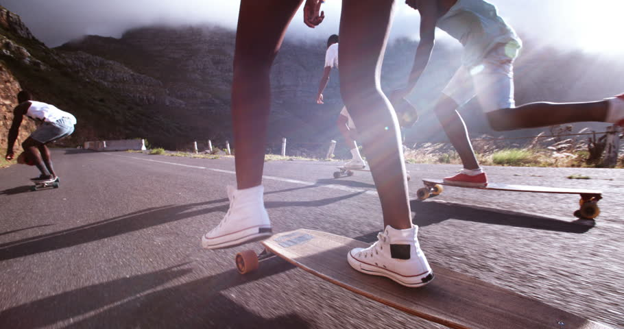 Mixed group of teenaged longboarders racing each other downhill on a mountain road in Slow Motion | Shutterstock Video #9517565