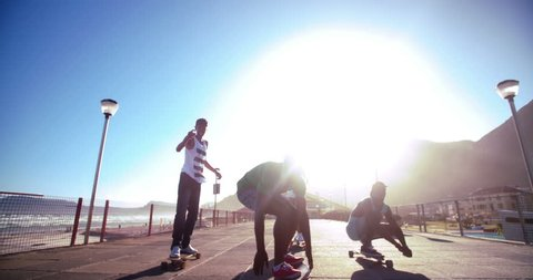 Rear view of a group of teenage students walking on a built structure carrying skateboards in Slow Motion