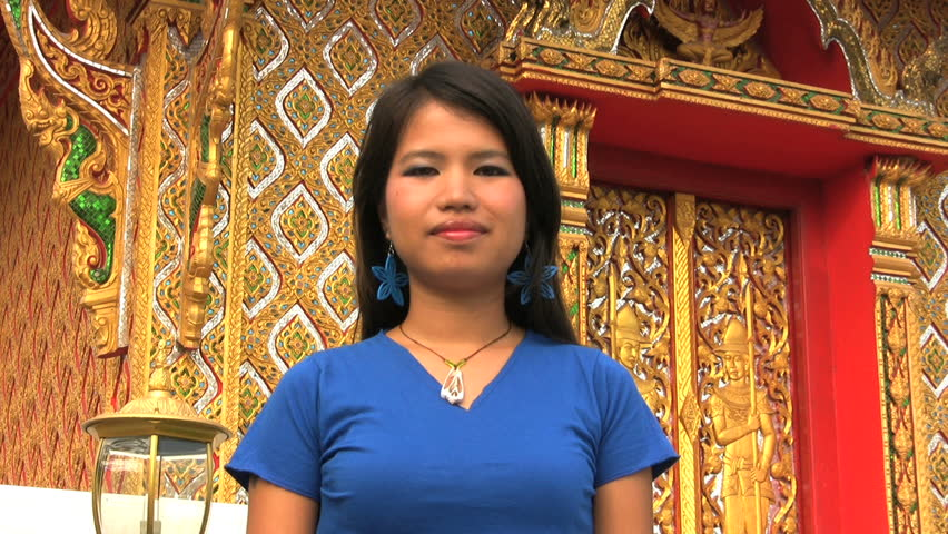 "A pretty Thai girl demonstrates a typical Thai greeting called the ""wai"" as she stands in front of a Buddhist temple in Bangkok, Thailand."