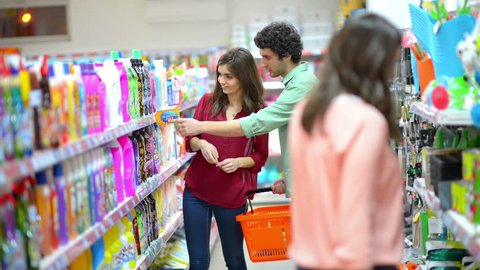 Happy woman showing to a man some cleaning product in supermarket