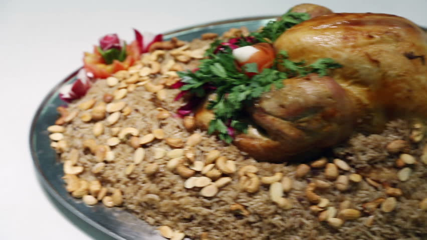 Serving rice and chicken meal, Kabsa. Kabsa is a family of mixed rice dishes that are served mostly in the middle east.These dishes are mainly made from a mixture of spices, rice, meat and vegetables