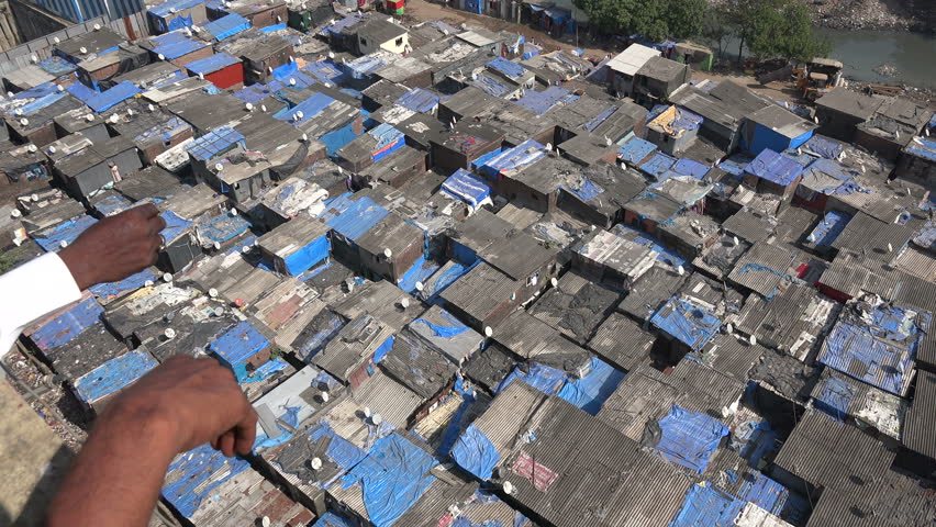 A man points at slum houses in Mumbai. The rooftops are made of corrugated sheet.