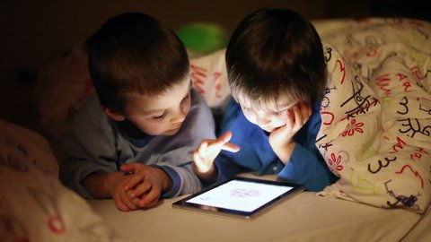 Cute little brothers, playing on tablet in bed at night