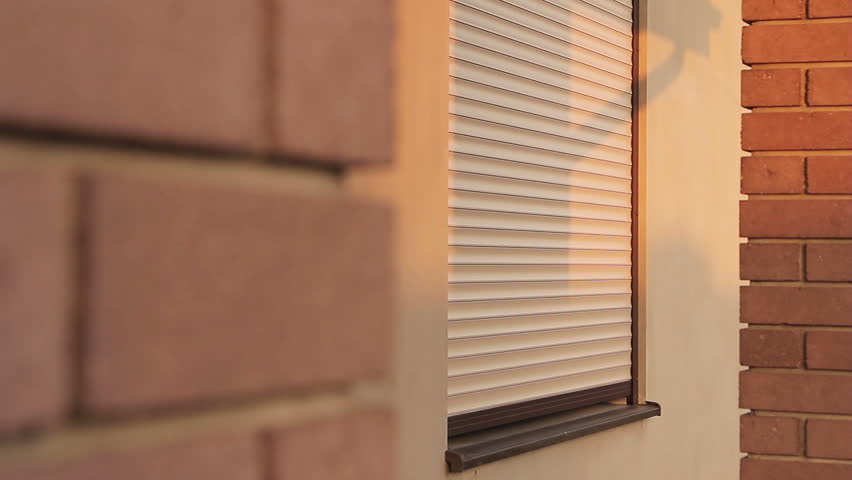 Rolling shutter window opening in the morning sunshine