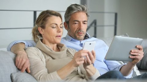 Mature couple at home using tablet and smartphone