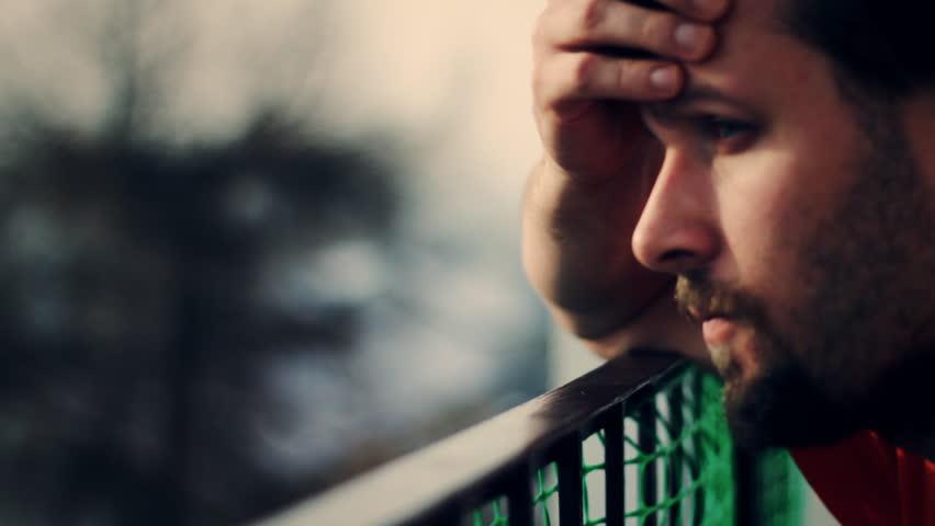 Sad man on the patio, face closeup