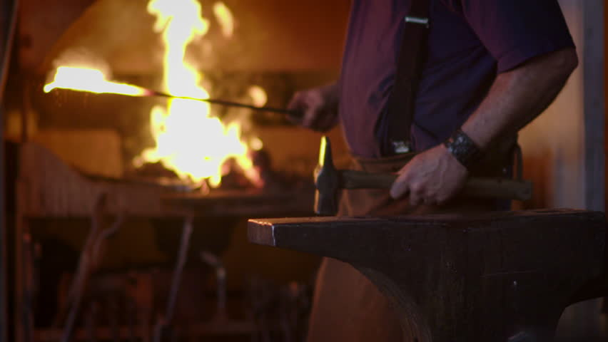 Blacksmith brings dripping hot metal from furnace and creates a shower of sparks as he beats a piece of white hot metal with a hammer on an anvil.  Close up recorded at 180fps.