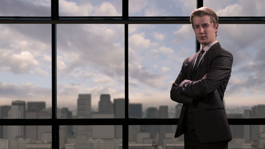 Smiling, confident, young businessman standing in front of city skyline view. With room for copy.
