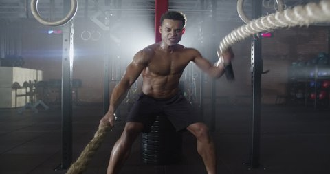 Medium shot slow mo zoom-in, zoom-out young man exercising arms and shoulders with rope in gym