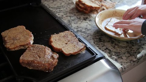 A woman makes delicious french toast for breakfast in the morning