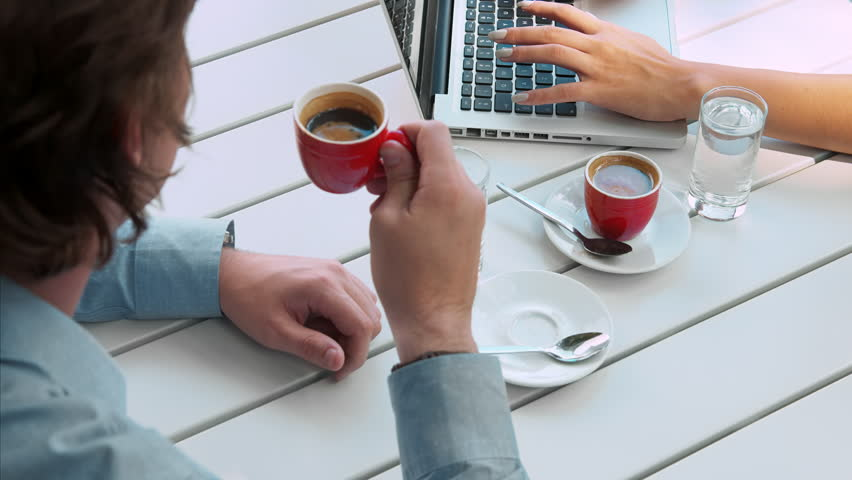 Above view angle of a young casual and focused business team working with modern laptop, making notes and brainstorming over morning coffee and morning news paper.  #9716060