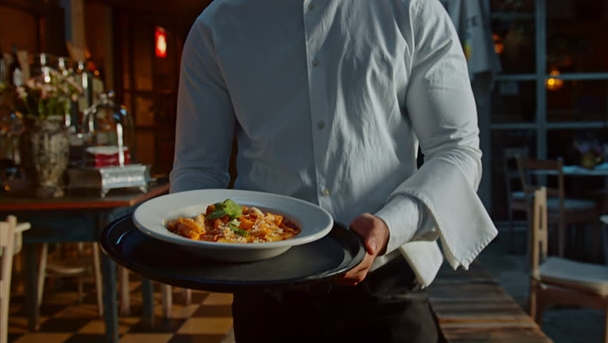 Waiter with a tray of food in the restaurant at night, walking to customer. Steadicam shot.