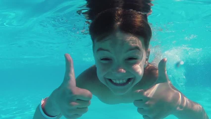 Cute teen boy dives in blue pool with open eyes | Shutterstock HD Video #9735068