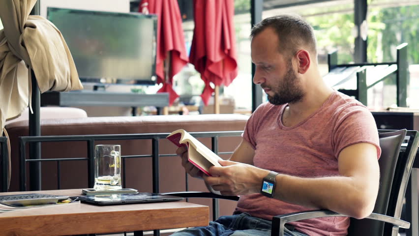 Young man reading book sitting in cafe in city  | Shutterstock HD Video #9742331