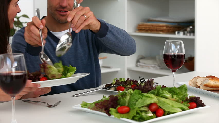 Man serving salad to his wife during lunch in the kitchen