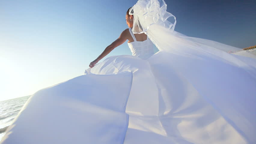 Beautiful bride in her wedding dress walking on the beach where she married