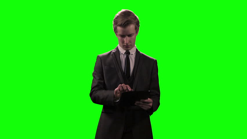 Young executive businessman using tablet device against greenscreen