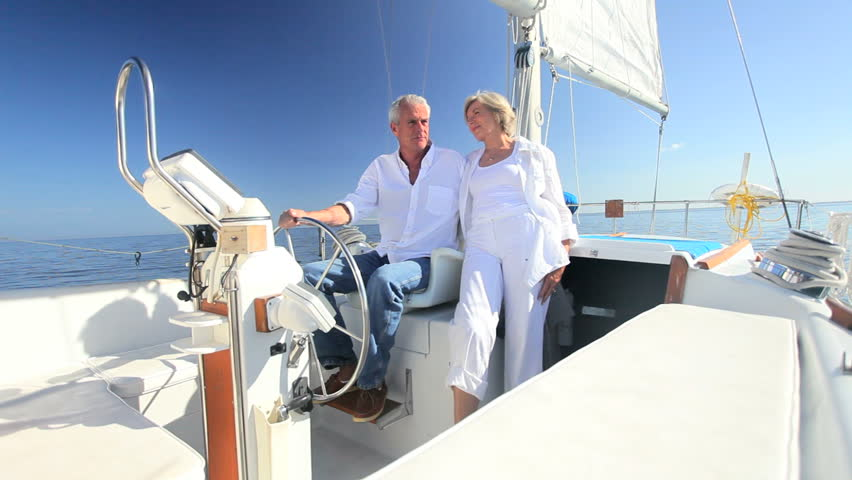 Healthy retired couple steering a course aboard their luxury sailing boat