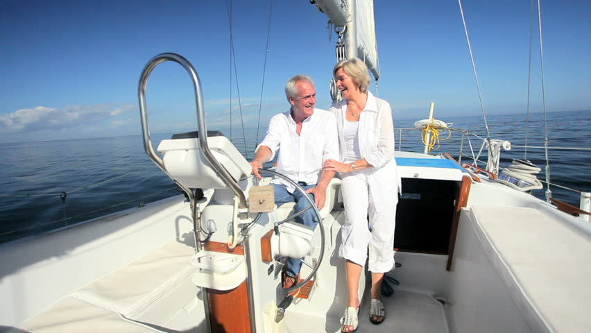 Healthy retired couple enjoying their leisure aboard their luxury sailing boat