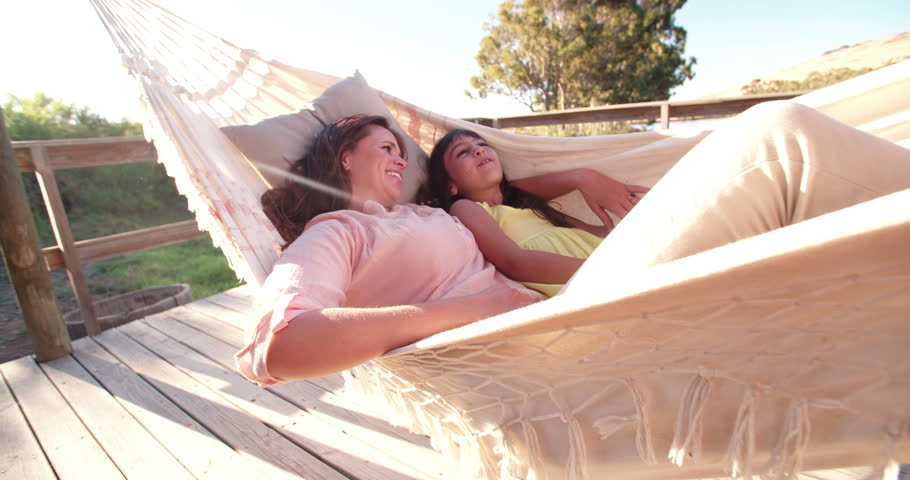 Happy mother and daughter relaxing together in a hammock with sun flare, Slow Motion