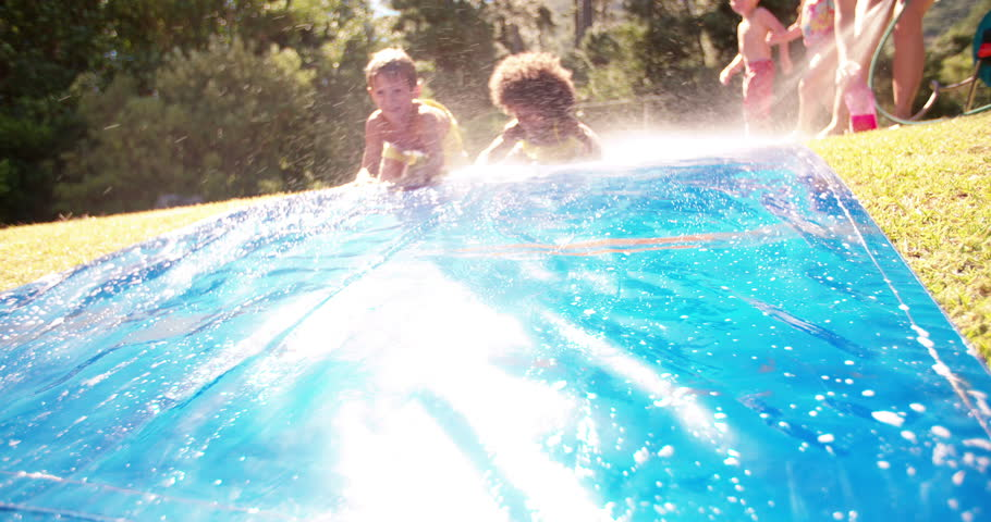 Laughing little Afro girl and friends playing together on a water slide in their yard in the sun