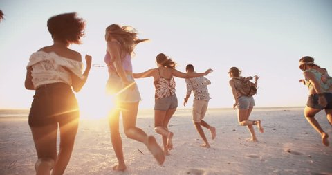 Group of young friends running in Slow Motion together on a beach at the water's edge at sunset