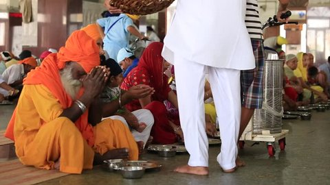 AMRITSAR, INDIA - SEPTEMBER 27, 2014: Unidentified poor indian people eating free food at a soup kitchen in the Sikh Golden Temple