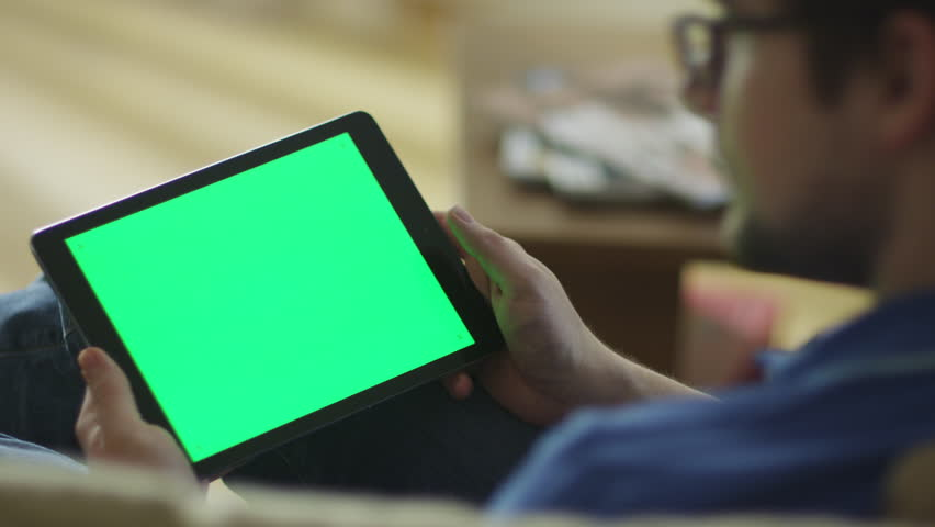 Man is Laying on Couch at Home and Using Tablet with Green Screen in Landscape Mode. Shot on RED Cinema Camera in 4K (UHD). | Shutterstock HD Video #9813047
