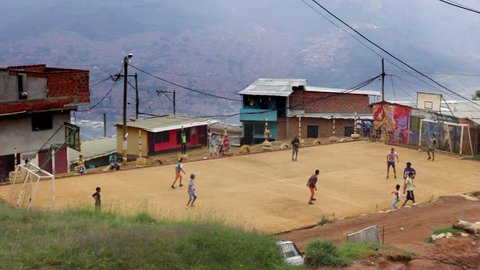 MEDELLIN, COLOMBIA - MAY 2015: Teenagers play football on gravel pitch in the neighborhood El Pinar, Santo Domingo in Medellin.