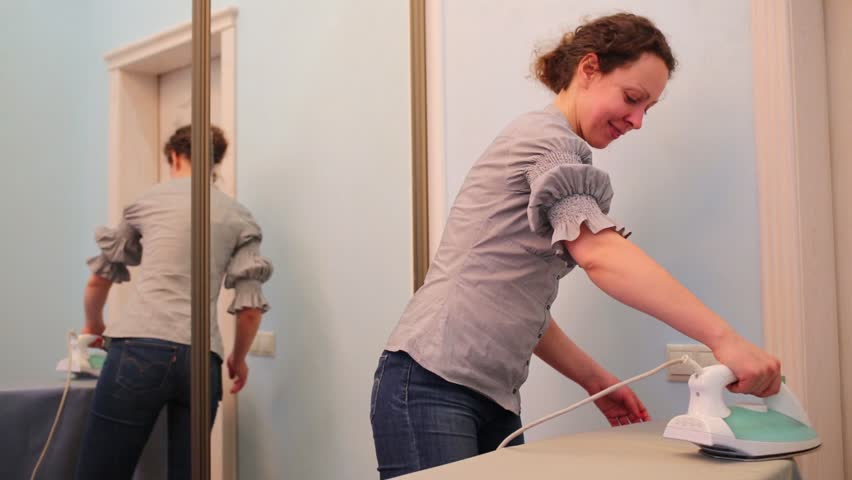 Housewife in gray blouse and jeans irons in room with mirror