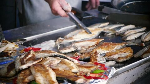 SLOW MOTION: the cook makes grill fish at Karaköy Fish Market (Istanbul, Turkey). The chef toils over an open grill frying fish. Cooking mackerel fillet at grill for fish durum. Street food in Turkey.